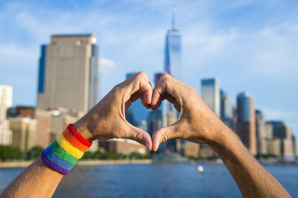 Hands wearing gay pride rainbow sweat band making heart symbol i